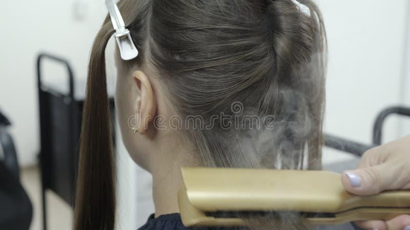Il parrucchiere fa la laminazione dei capelli in un salone di bellezza per una ragazza con capelli castana fotografie stock libere da diritti
