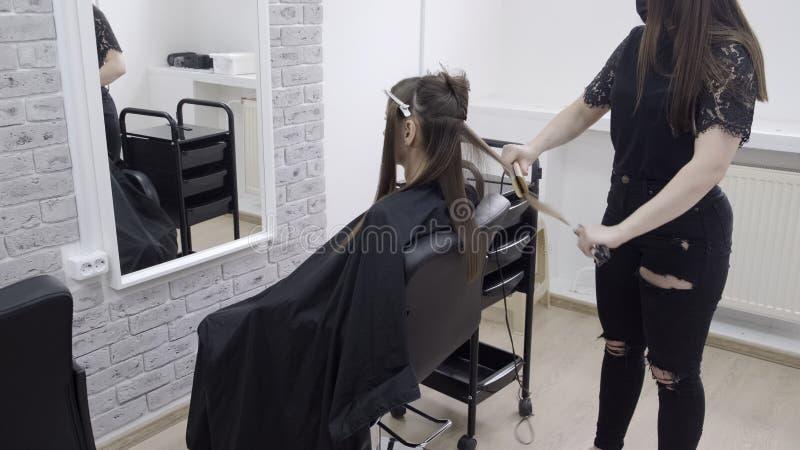 Il parrucchiere fa la laminazione dei capelli in un salone di bellezza per una ragazza con capelli castana immagine stock