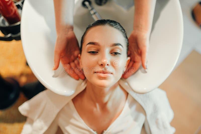 Il parrucchiere lava i capelli del cliente, vista superiore fotografia stock