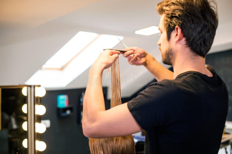 Il parrucchiere maschio sta tagliando i capelli fotografia stock libera da diritti