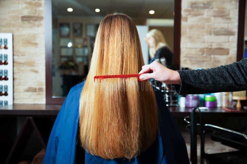 Il parrucchiere pettina i capelli lunghi della giovane donna fotografie stock