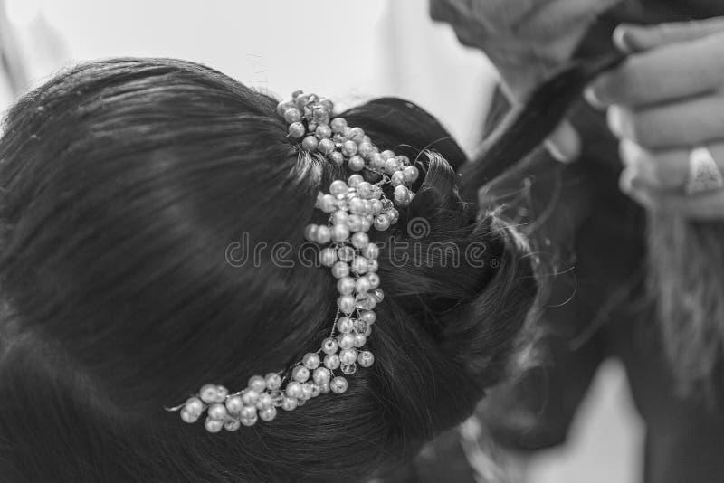 Il parrucchiere prende un'acconciatura del ` s della sposa sul suo giorno delle nozze immagini stock
