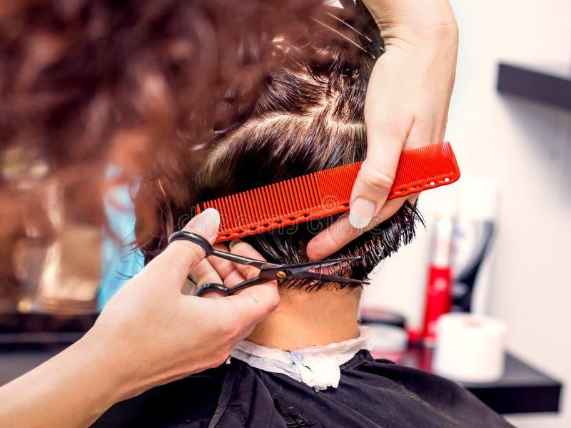 Il parrucchiere professionista fa l'acconciatura alla moda per la donna immagini stock libere da diritti