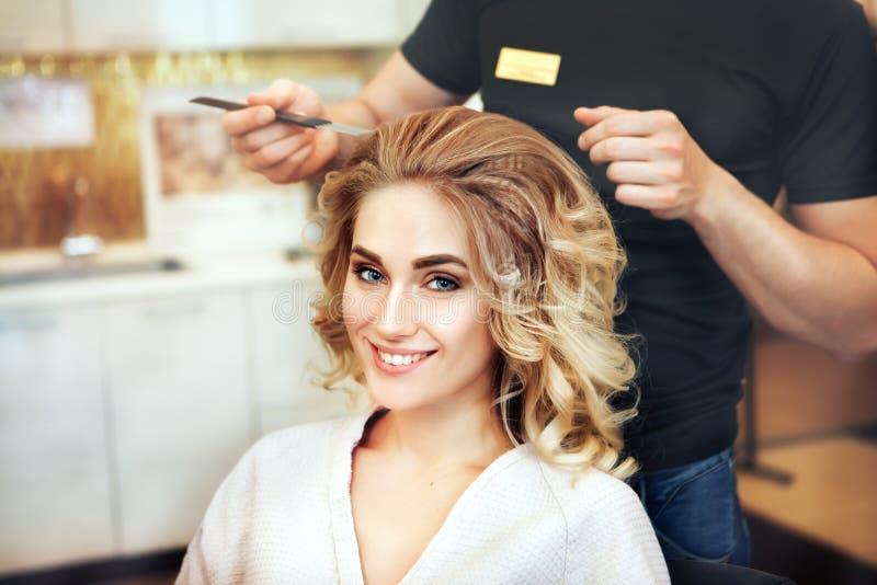 Il parrucchiere professionista fa l'acconciatura per un modello lungo dei capelli fotografia stock