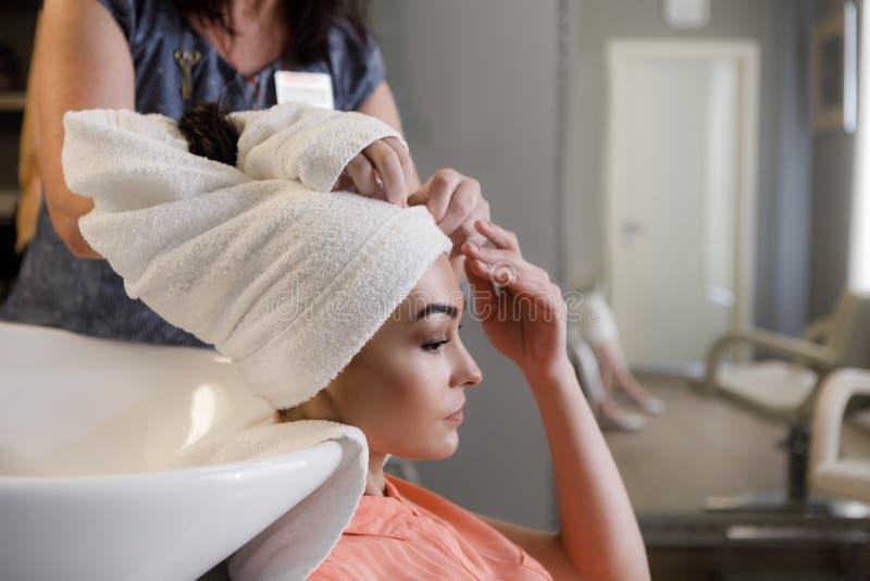 Il parrucchiere sta riparando l'asciugamano sulla testa della donna in salone immagine stock libera da diritti