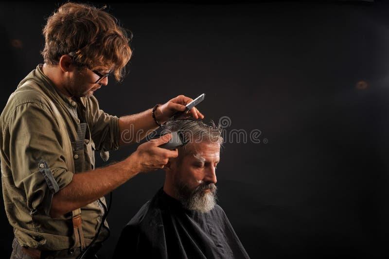 Il parrucchiere taglia l'anziano con una barba su un fondo scuro fotografia stock libera da diritti