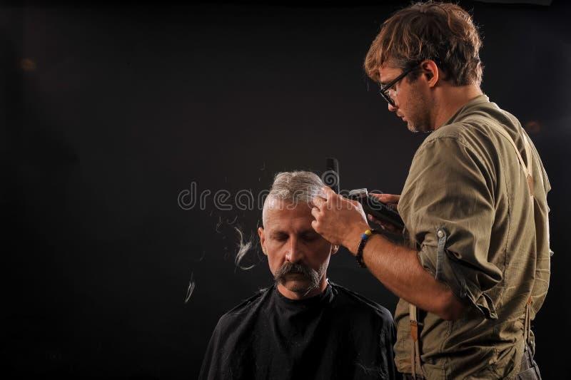 Il parrucchiere taglia l'anziano con una barba su un fondo scuro immagine stock libera da diritti