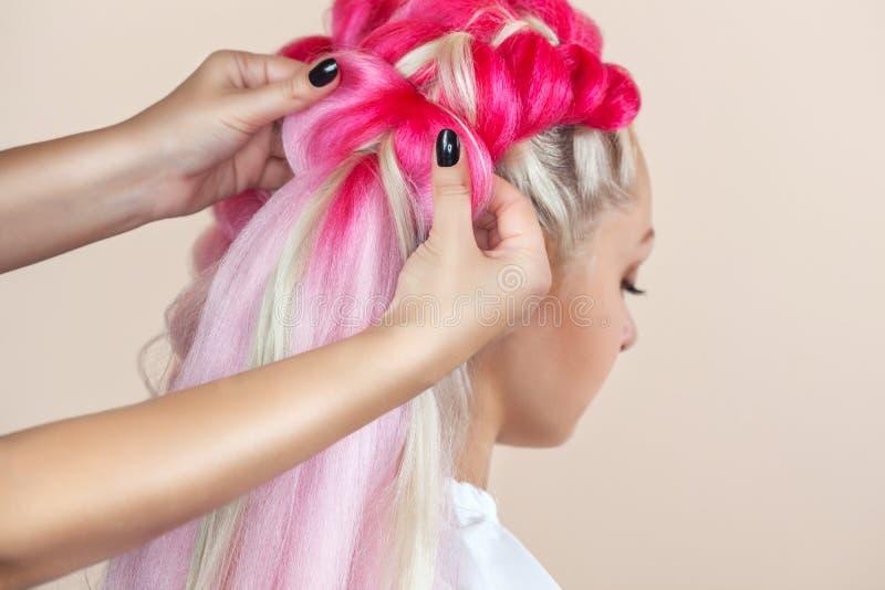 Il parrucchiere tesse le trecce con la bella bionda dei kanekalons rosa immagini stock