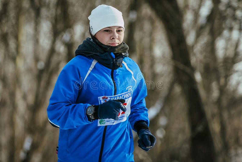 Il partecipante della ragazza della maratona funziona attraverso un primo piano di distanza fotografia stock