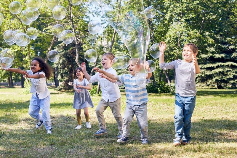 Il partito dei bambini al parco pubblico verde immagine stock