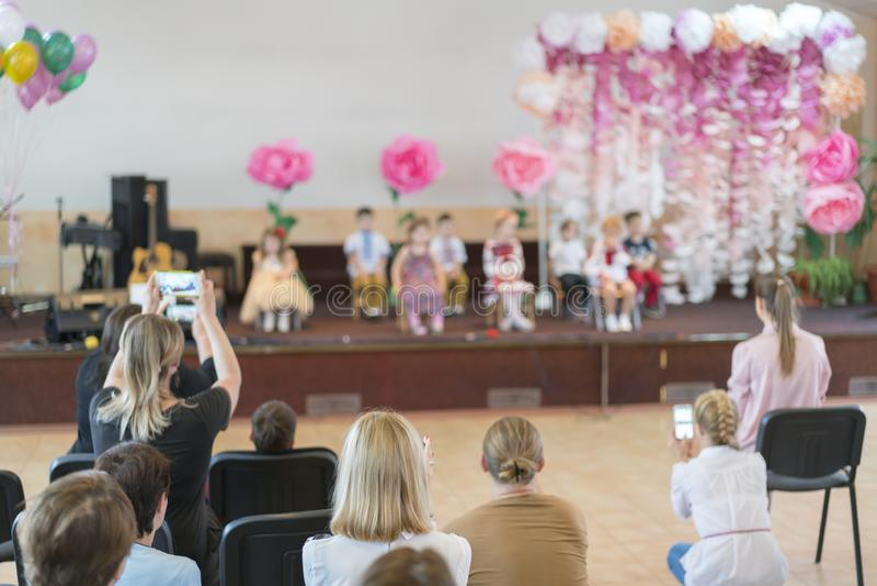 Il partito dei bambini a scuola primaria I bambini piccoli in scena nell'asilo compaiono nei genitori anteriori blurry fotografie stock libere da diritti