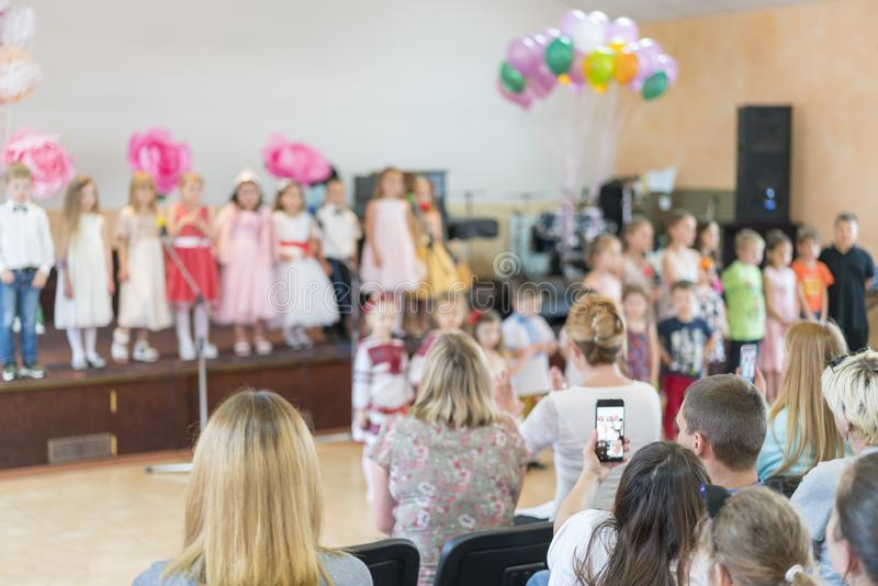 Il partito dei bambini a scuola primaria I bambini piccoli in scena nell'asilo compaiono nei genitori anteriori blurry fotografia stock libera da diritti