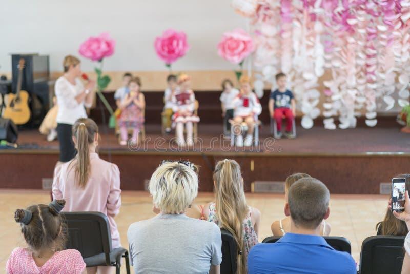 Il partito dei bambini a scuola primaria I bambini piccoli in scena nell'asilo compaiono nei genitori anteriori blurry fotografie stock