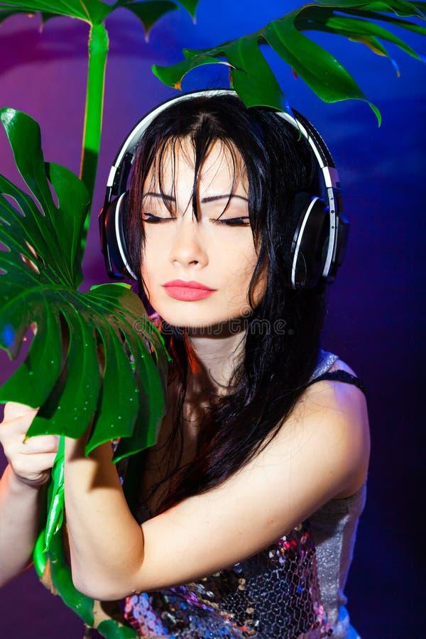 Il partito tropicale di verde della ragazza della discoteca dell'estate della spiaggia della cuffia del DJ castana lascia il gior fotografia stock libera da diritti