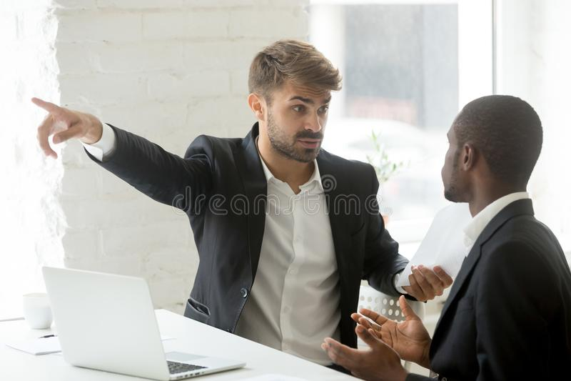 Il partner bianco maleducato che dice l'uomo d'affari nero esce il suo ufficio fotografie stock libere da diritti