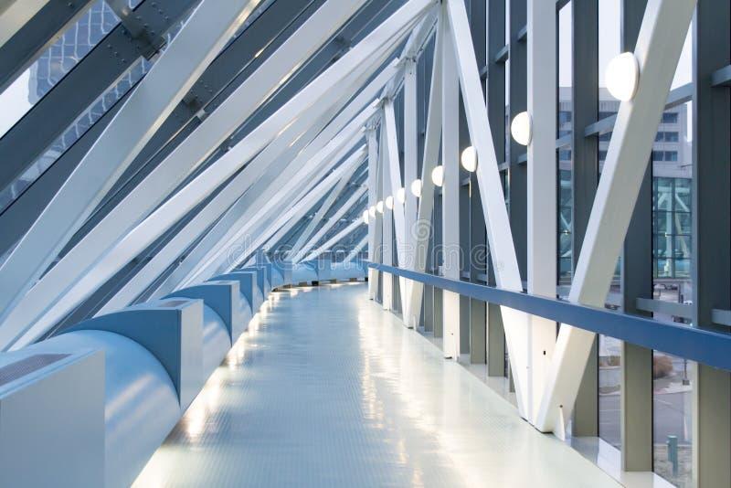 Il passaggio pedonale elevato futuristico emette luce morbidamente alla luce blu del giorno nuvoloso fotografia stock