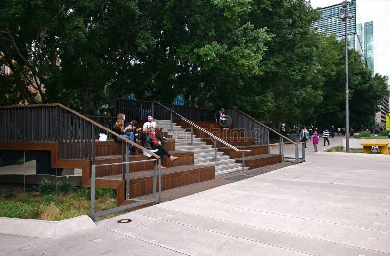 Il passaggio pedonale urbano delle merci allinea con la gente sulla disposizione dei posti a sedere del teatro sulla città univer immagine stock libera da diritti