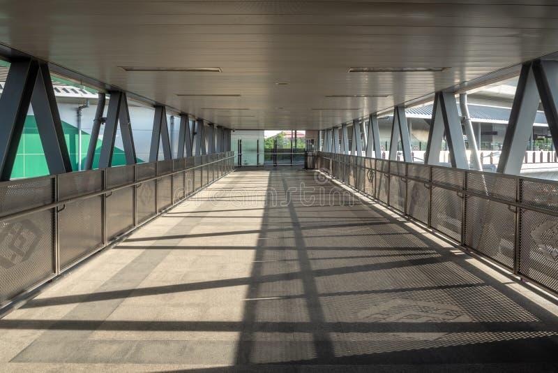 Il passaggio pedonale vuoto del ponte del passaggio con la ferrovia del ferro ed il tetto d'acciaio si collegano alla stazione di fotografie stock libere da diritti
