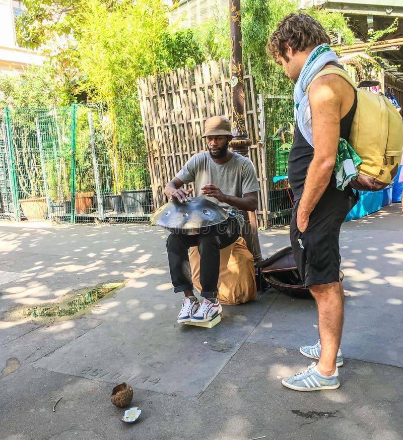 Il passante guarda il giocatore del tamburo d'acciaio a Parigi fotografie stock libere da diritti
