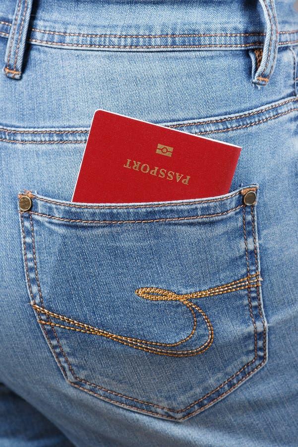 Il passaporto biometrico rosso in jeans intasca il primo piano immagine stock