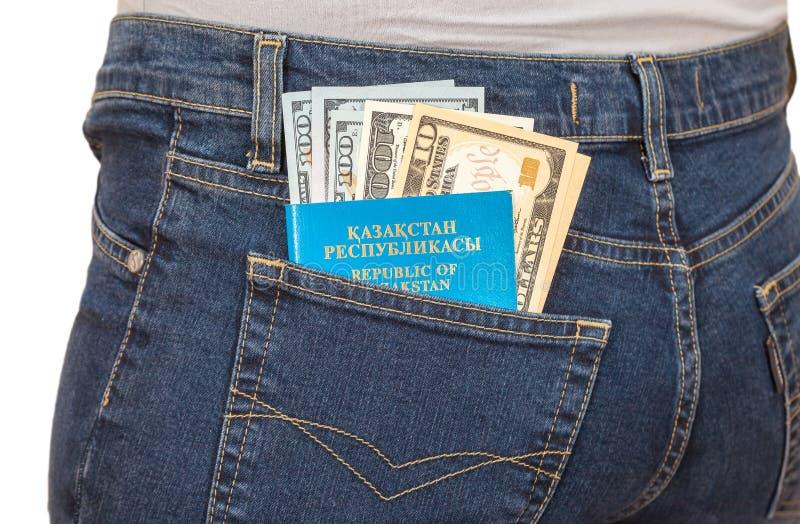 Il passaporto e le banconote in dollari del Kazakistan nei jeans posteriori intascano immagini stock libere da diritti