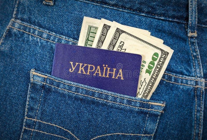 Il passaporto e le banconote in dollari ucraini nei jeans intascano immagini stock libere da diritti