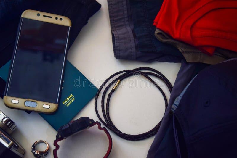 Il passaporto, gli occhiali da sole, la vecchia macchina fotografica, i jeans, la camicia, il braccialetto e gli occhiali da sole immagini stock libere da diritti