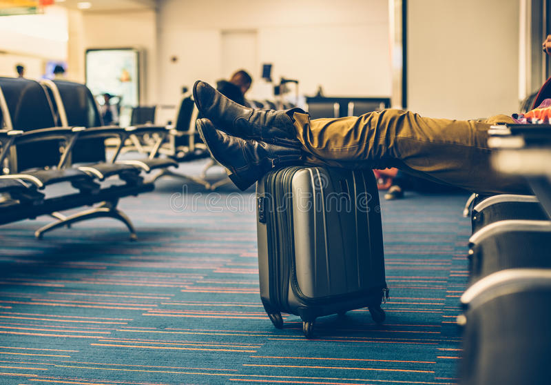 Il passeggero con continua i bagagli che aspettano il volo di ritardo nel terminale di aeroporto fotografia stock libera da diritti