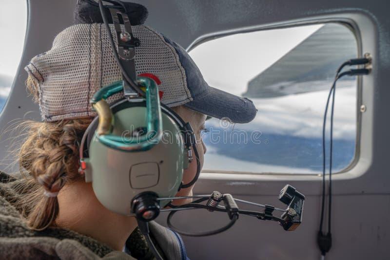 Il passeggero femminile guarda fuori la finestra mentre vola in un aereo d'Alasca di Bush immagine stock