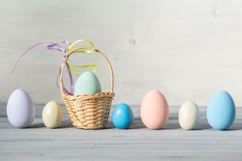 Il pastello di Pasqua ha colorato le uova ed il piccolo canestro su un fondo di legno leggero immagine stock libera da diritti