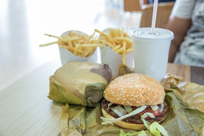 Il pasto dell'hamburger è servito con le patate fritte e la soda in un ristorante immagini stock libere da diritti