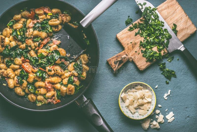 Il pasto vegetariano con gli gnocchi della patata, gli spinaci e le verdure sauce in padella sulla tavola rustica immagine stock libera da diritti
