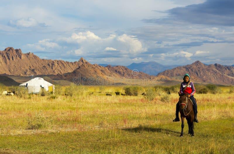 Il pastore non identificato monta il cavallo vicino al suo yurt immagine stock libera da diritti