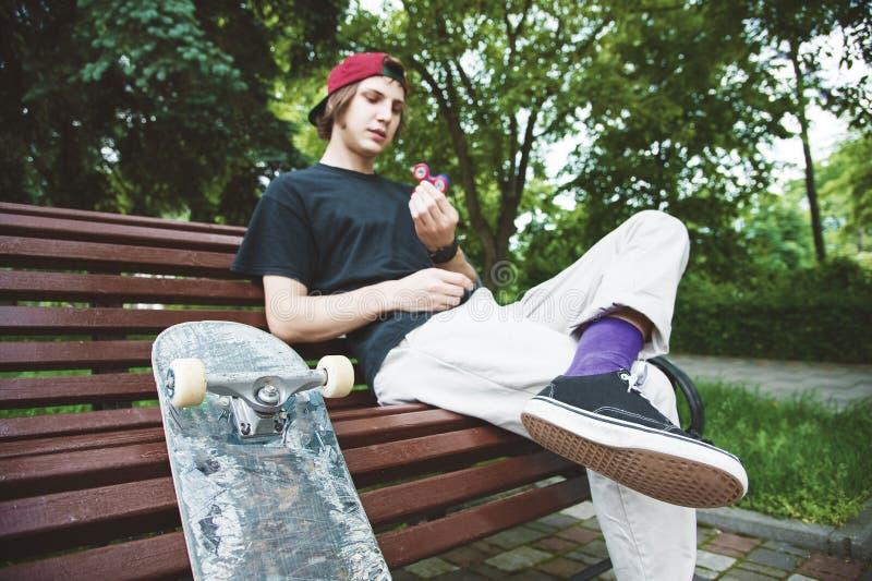 Il pattinatore dai capelli lunghi dei pantaloni a vita bassa in un cappuccio si siede su un banco e fila su un rotazione-filatore immagine stock