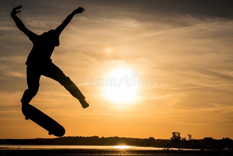 Il pattinatore salta contro il bello tramonto arancio fotografia stock libera da diritti