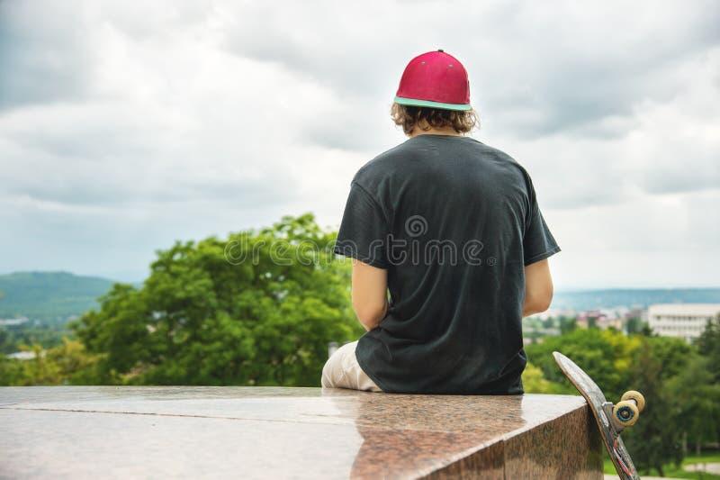 Il pattinatore si siede con la sua la parte posteriore e ritiene accanto al pattino immagine stock