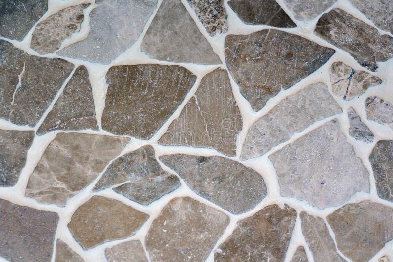Il pavimento di pietra è decorato con vario mosaico geometrico, mattonelle blu, rosse, bianche, nere Modello caotico geometrico d fotografia stock