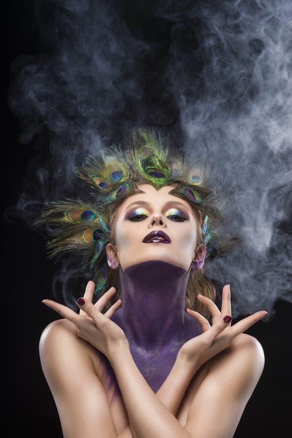 Il pavone d'uso della bella grande ragazza del seno mette le piume a in suoi capelli a fotografie stock libere da diritti