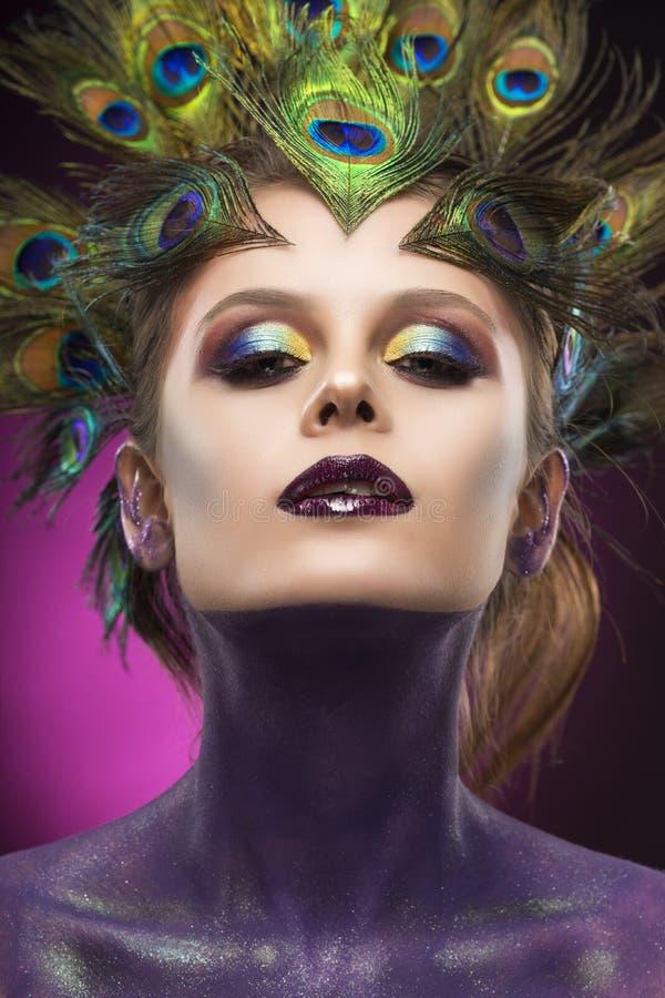 Il pavone d'uso della bella grande ragazza del seno mette le piume a in suoi capelli a immagini stock libere da diritti