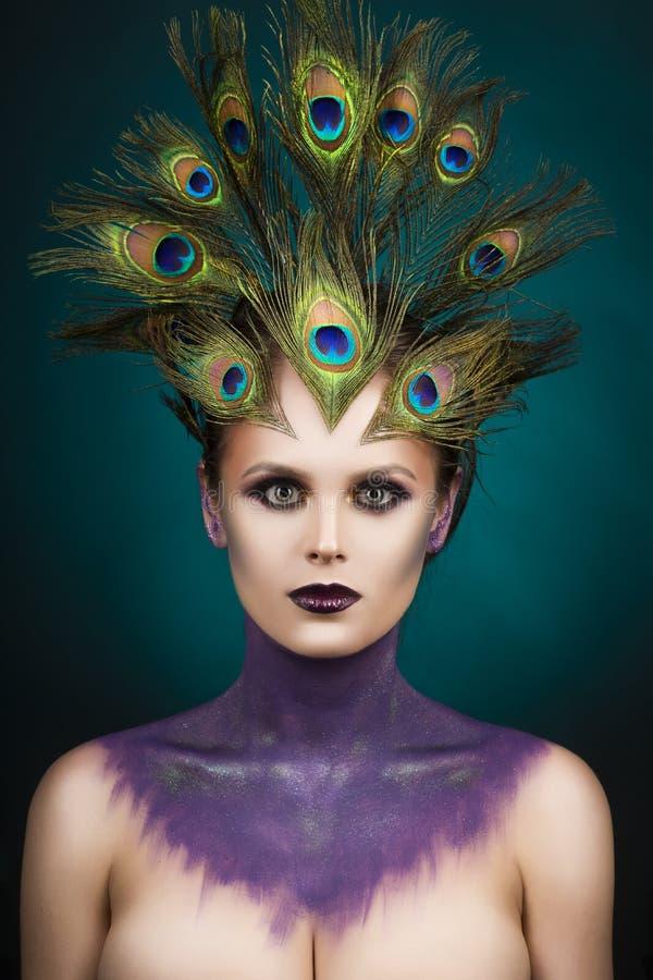 Il pavone d'uso della bella grande ragazza del seno mette le piume a in suoi capelli a immagine stock