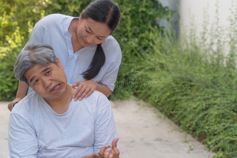 Il paziente è ictus o il colpo causato da ipertensione e dall'obesità, sedentesi in sedia a rotelle lui topo è PA facciale fotografia stock