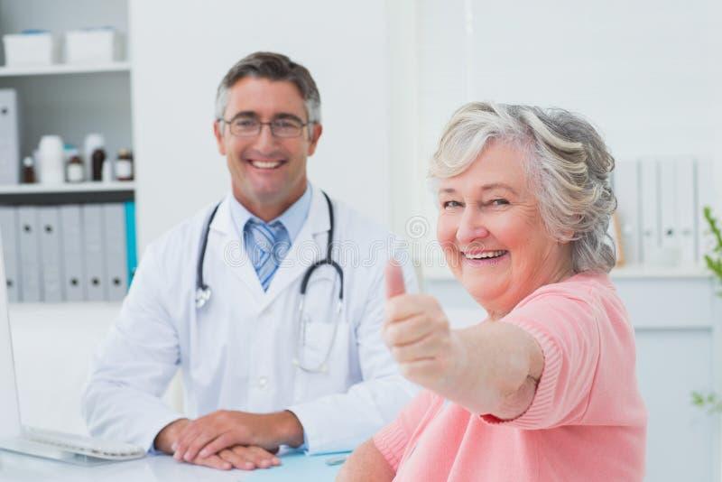 Il paziente che mostra i pollici aumenta il segno mentre si siede con medico fotografie stock libere da diritti