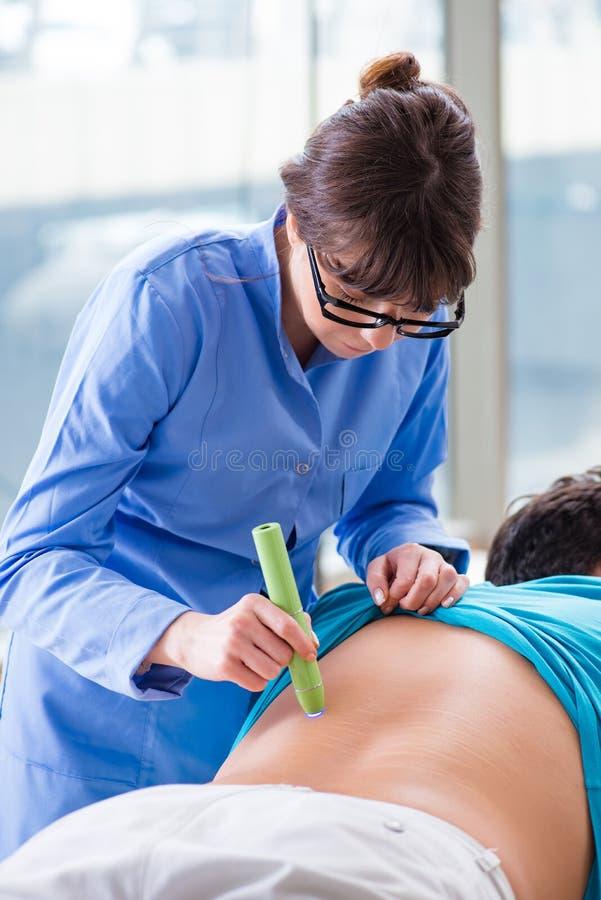 Il paziente in clinica che subisce rimozione della cicatrice del laser fotografie stock