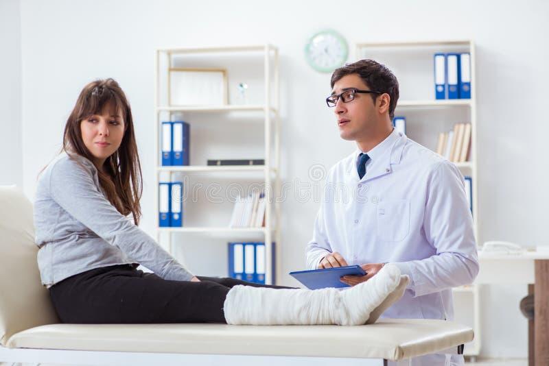 Il paziente d'esame di medico con la gamba rotta immagini stock