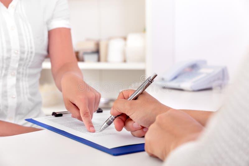 Il paziente femminile sta firmando alcuni documenti fotografie stock