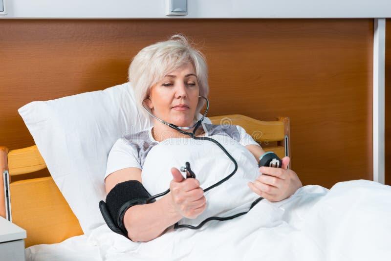 Il paziente femminile sta misurando la pressione arteriosa facendo uso di un medica fotografia stock libera da diritti