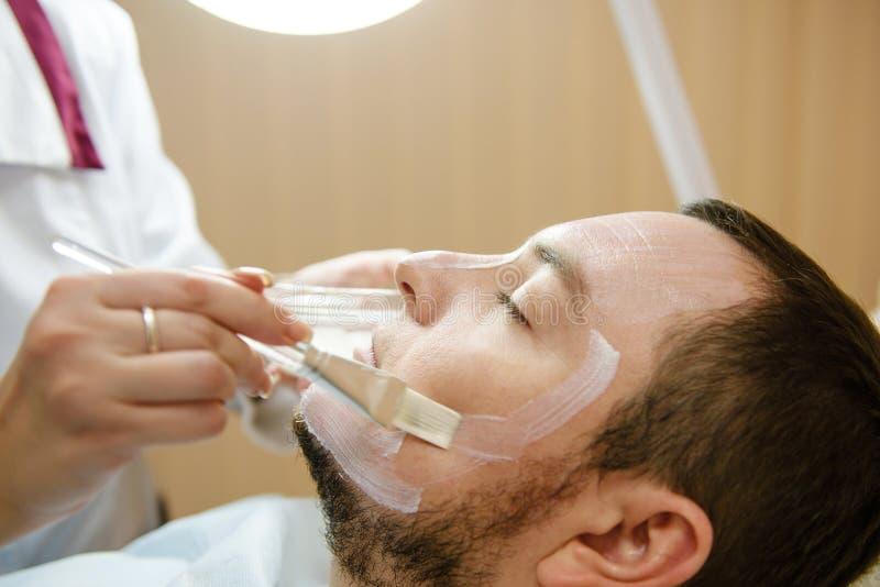 Il paziente maschio ottiene il trattamento facciale nella clinica di bellezza immagini stock libere da diritti