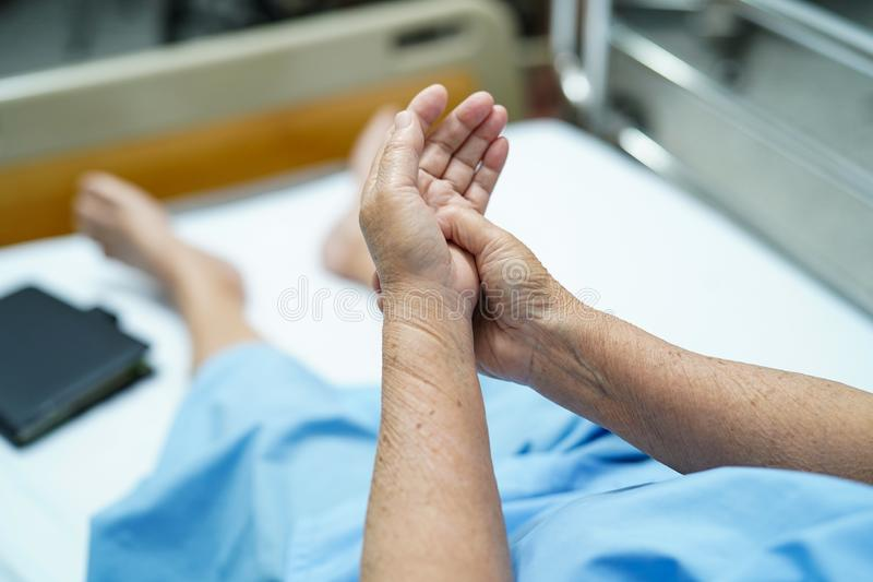 Il paziente senior o anziano asiatico della donna della signora anziana ritiene il dolore la sua mano sul letto in ospedale di cu fotografie stock