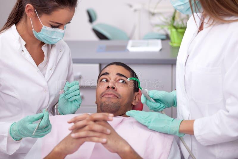 Il paziente spaventato al dentista fotografia stock