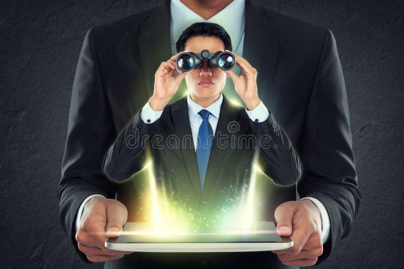 Il pc della compressa della tenuta dell'uomo d'affari e fuori equipaggia con il binocolo fotografie stock